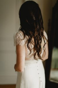 A caption of the back of Katies long hair she is wearing her wedding dress as she prepares to go the her ceremony