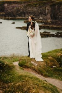 The bride and groom stand on the cliff edge and look out to the sea in Dingle Co Kerry