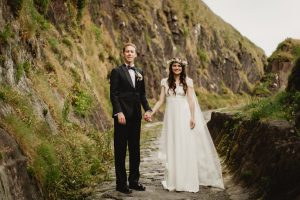 The bride and groom walk down Doonshean beach to take wedding photographs in Dingle Co Kerry