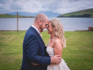 Sinead and Micheal embrace in front of stunning scenery in Dingle county kerry